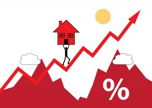 A house symbol being carried up a rising graph. A metaphor on rising house values and cost.